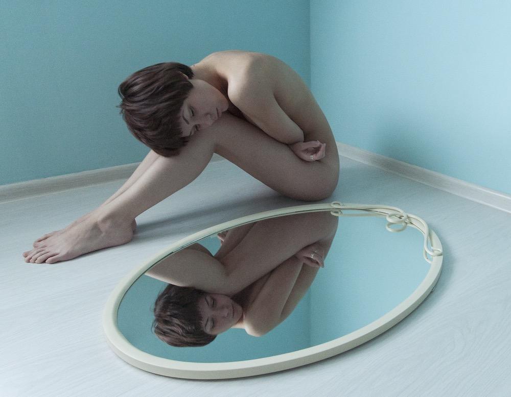 Mujer joven observando su imagen desnuda en un espejo.